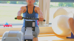 Brunette woman working out on row machine Footage