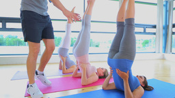 Three women stretching backs at yoga class Footage
