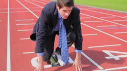 Businessman ready to run in starting block Filmmaterial