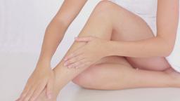 Woman rubbing cream onto legs Footage