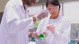 Two chemists experimenting with the green liquid Stock Video Footage