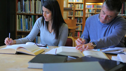 Woman and man studying in the library Footage
