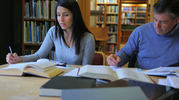 Mature students doing assignment in library Footage