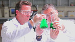 Two chemists experimenting with the green liquid i Stock Video Footage