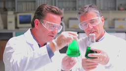 Two chemists experimenting with the green liquid i Footage