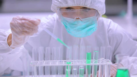 Chemist adding green liquid to test tubes Stock Video Footage