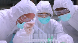 People in protective suits adding green liquid to  Footage