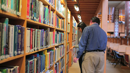 Woman and man choosing book Stock Video Footage