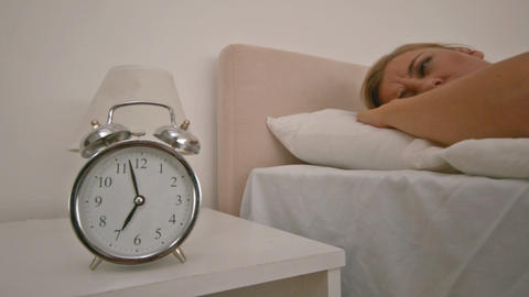 Blond woman pushing the alarm clock Stock Video Footage