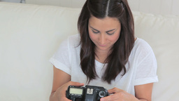 Woman sitting on the couch viewing the photos Stock Video Footage