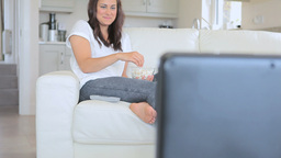 Smiling woman sitting on the sofa while watching T Footage
