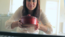 Video of brunette woman putting pressure cooker in Footage