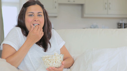 Video of woman eating popcorn while laughing Footage
