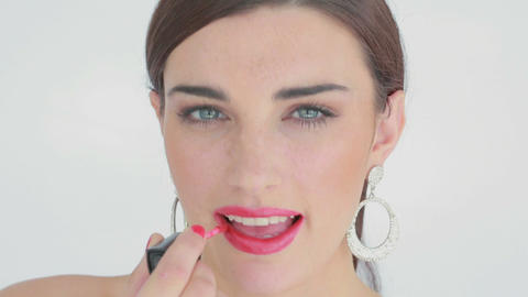 Woman applying pink lip gloss Live Action
