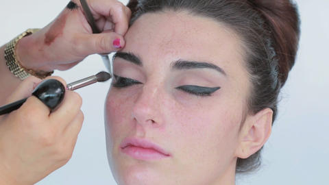 Make up artist applying eye shadow to model Footage