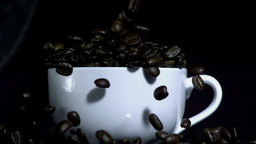 Coffee beans falling into overflowing cup Footage