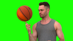 Man spinning the basketball on his finger on green Footage