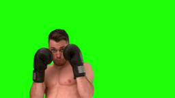 Focused man practicing boxing on green background Footage