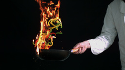 Peppers burning in a pan with big flame in slow mo Footage