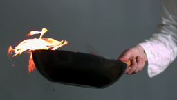 Chef tossing flaming wok of peppers Stock Video Footage