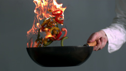Chef tossing flaming wok of peppers ビデオ