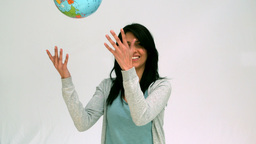 Woman throwing globe in the air Footage