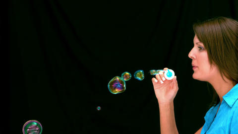 Brunette woman blowing bubbles Footage