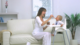 Mother feeding her baby in living room Stock Video Footage