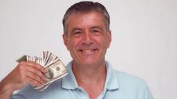 Smiling man waving bills Footage