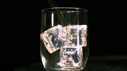 Whiskey being poured into a glass with ice cubes Stock Video Footage