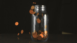 Cents filling up a glass jar Live Action