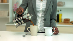 Woman adding milk to coffee in the kitchen Stock Video Footage