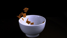 Wheat cereal squares being poured into a bowl Footage