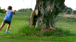 Two children running around a tree playing chasing Stock Video Footage