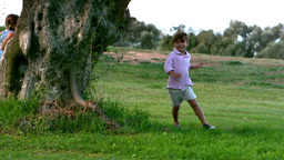 Two children running around a tree playing chasing Footage