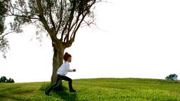 Little girl running around a tree Footage