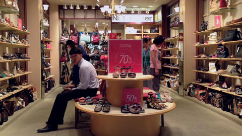 People looking at shoes at shoe store Footage
