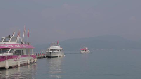 close shot & pan sun moon lake - people boarding b Footage