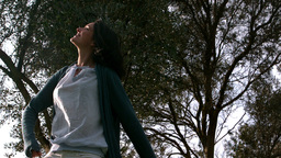 Woman turning around under tree Stock Video Footage