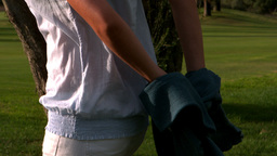 Woman taking jacket off in park Footage