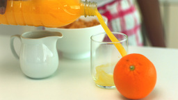 Orange juice being poured into a glass at breakfas Footage