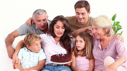 Family blowing candles on chocolate cake Stock Video Footage