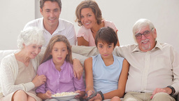 Multigeneration family on couch watching tv Stock Video Footage