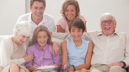 Multigeneration family on couch watching tv Footage