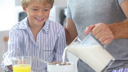 Father pouring milk for sons cereal Stock Video Footage