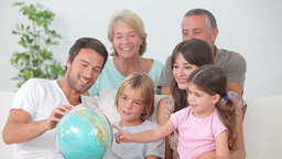 Multigeneration family all looking at globe Stock Video Footage