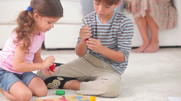 Siblings playing board game on the floor Stock Video Footage