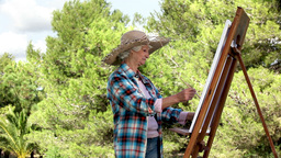 Elderly woman painting in the park Footage