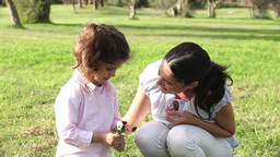 Little girl smelling a flower with mother Footage