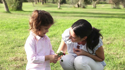 Little girl smelling a flower with mother Stock Video Footage